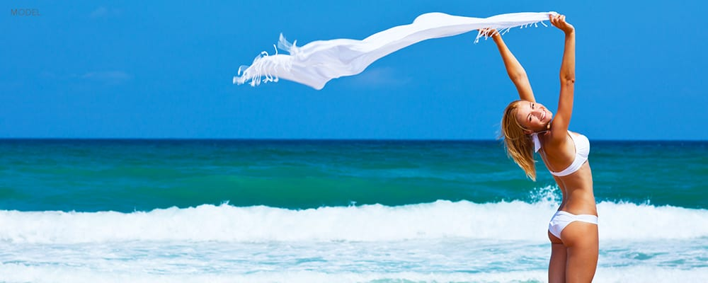 Happy Woman in Bikini Holding up Shawl Blowing in the wind on a Beach