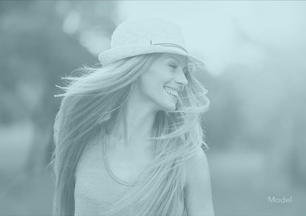 Female Model Smiling and Wearing a Hat with a Pale Blue Filter