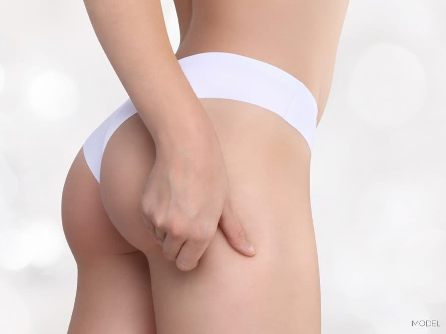 Female Buttocks In White Underwear Pinching to Show No Cellulite