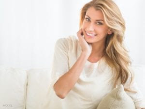 Blond Ocala Woman With Beige Blouse Sitting on Couch Considering A Non-surgical Facelift